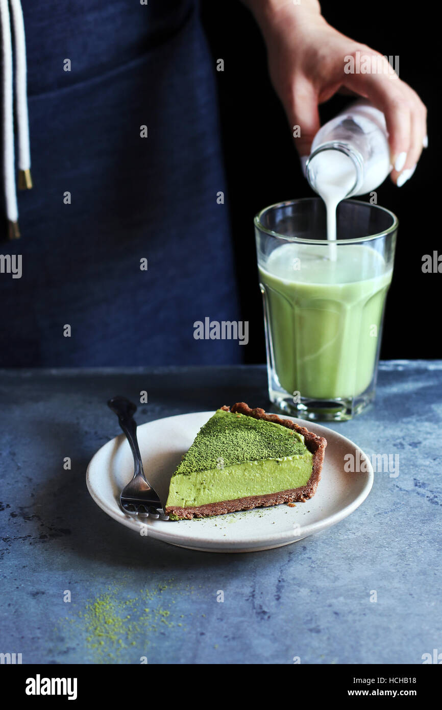 A slice of matcha tart with cream cheese filling on a plate.Female hand pouring coconut milk into matcha latte on - Stock Image