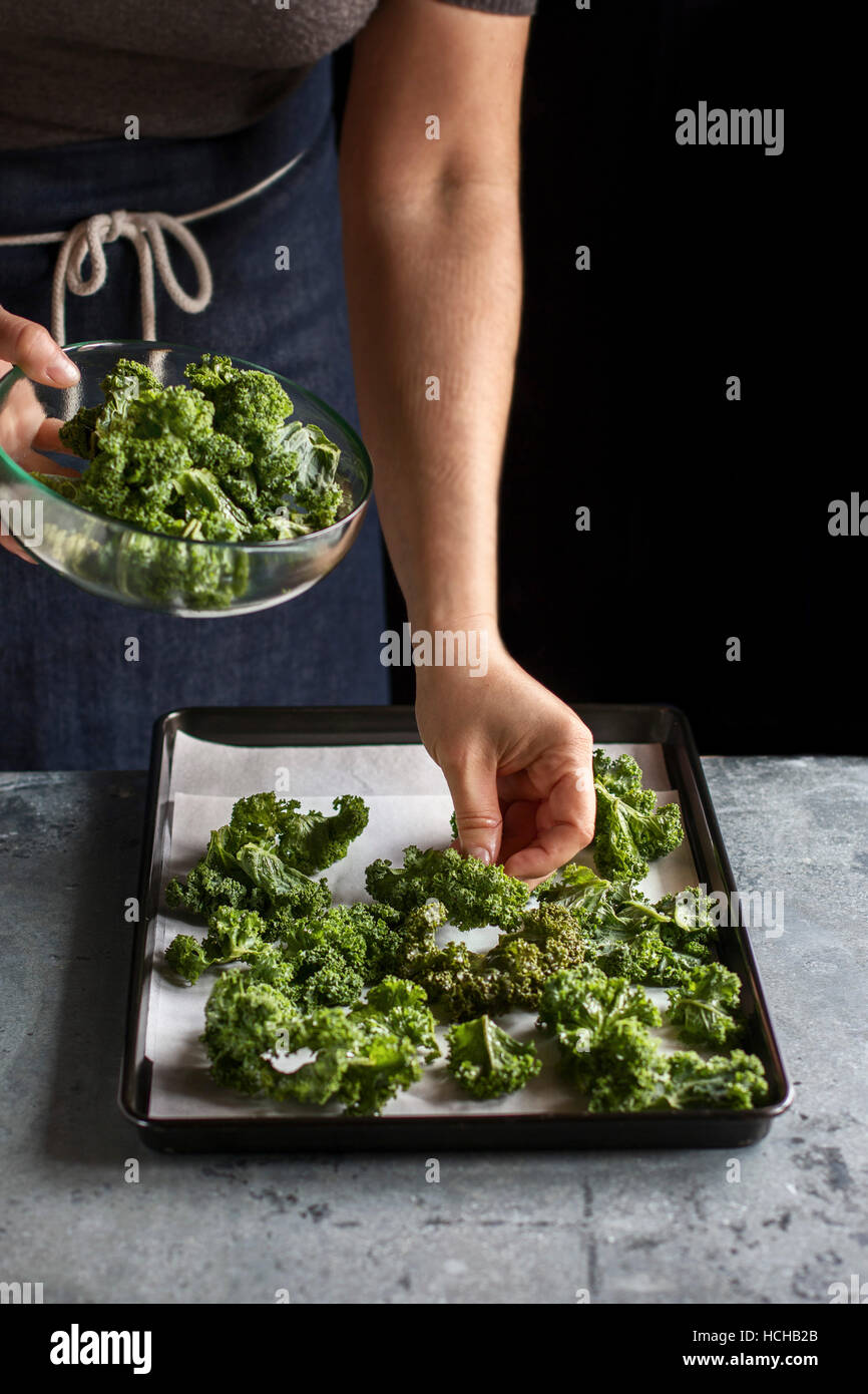 Making kale chips.Female hands placing cabbage leaves on a tray. - Stock Image