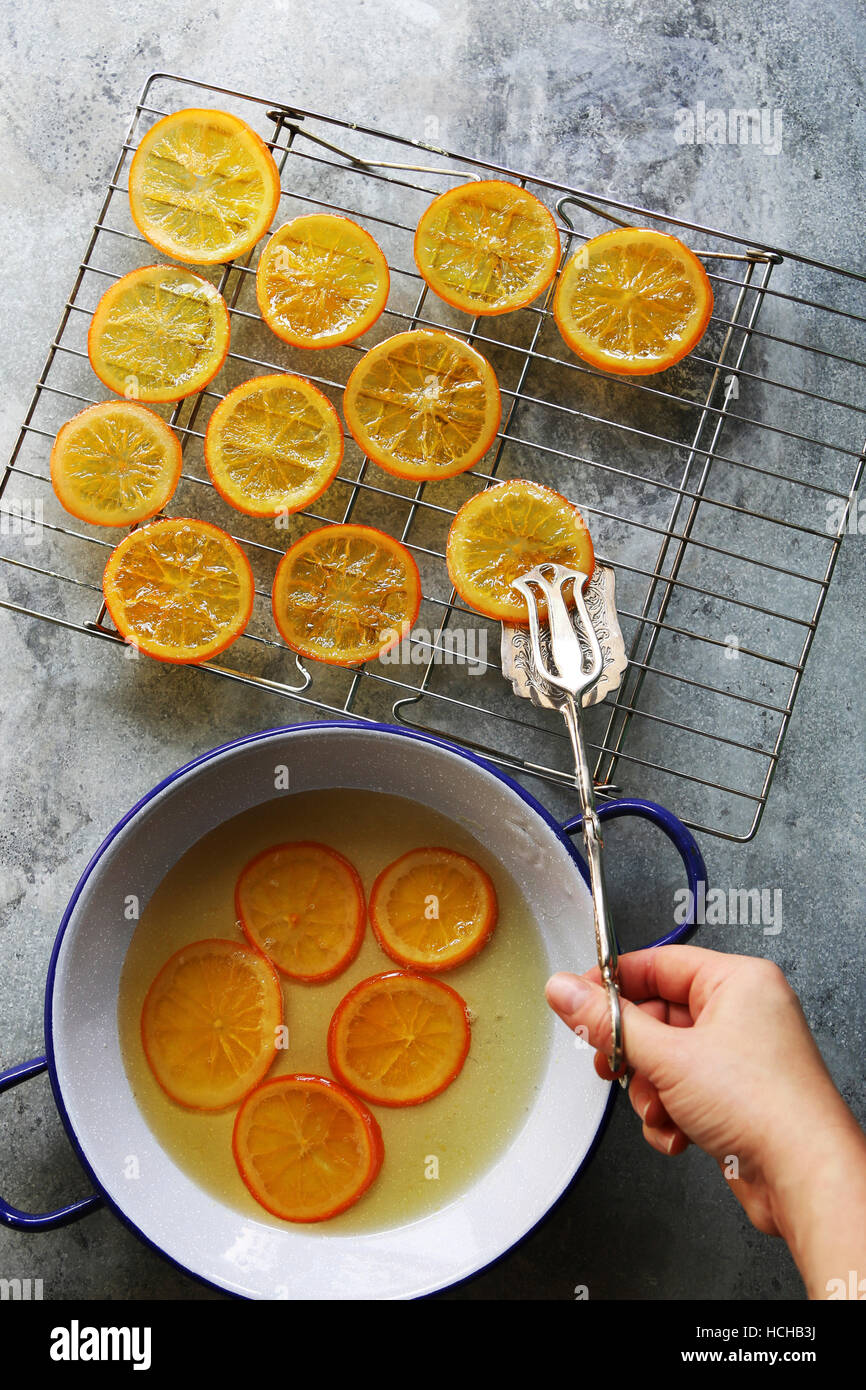 Female hand placing a slice of candied orange on a grill to dry.Top view - Stock Image