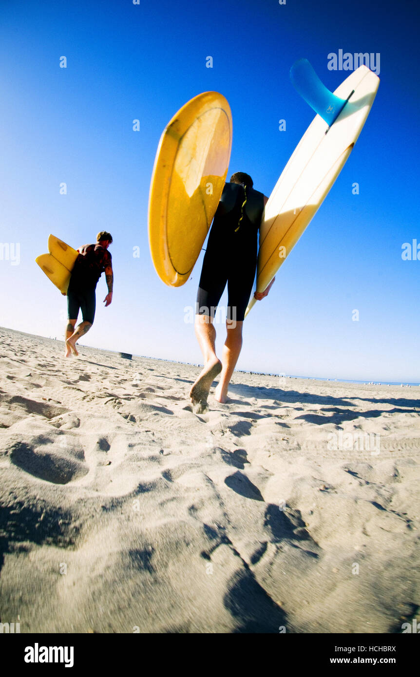 Early morning sun shines on two young men carrying surfboards on the beach in Oceanside, California - Stock Image