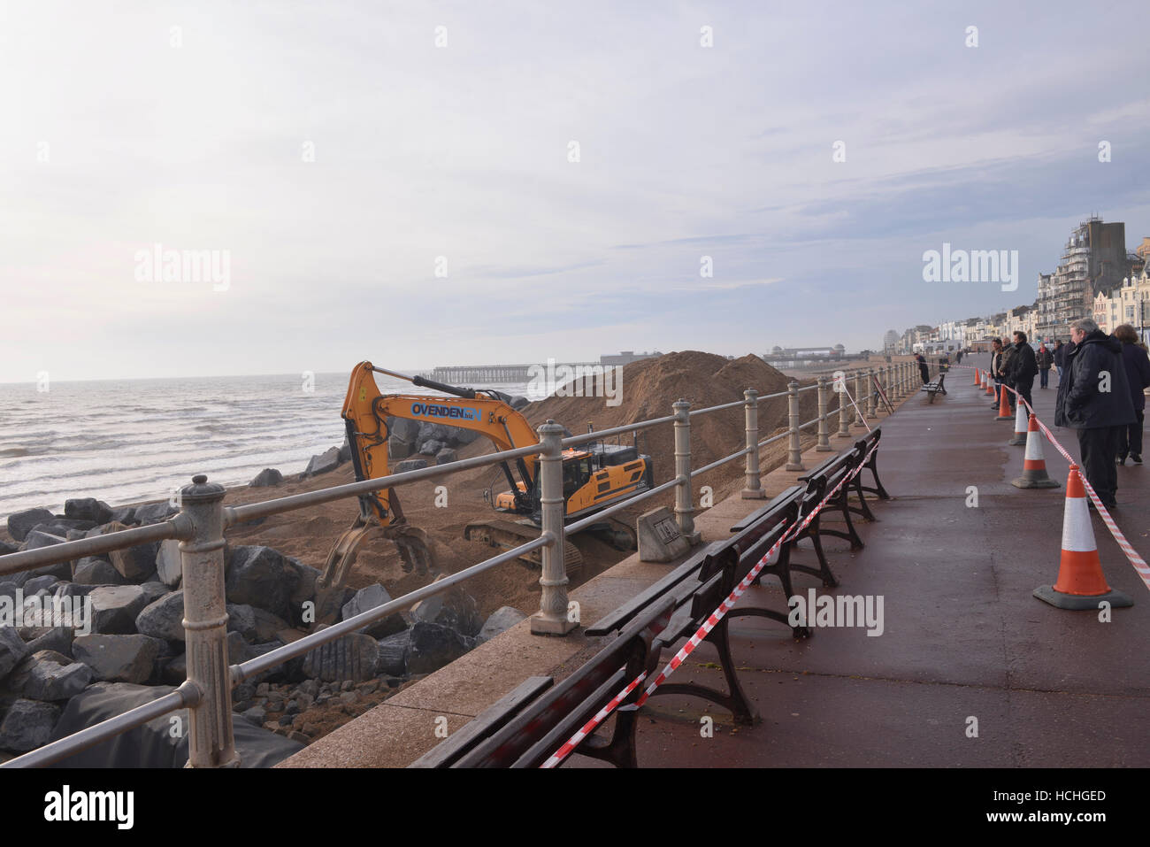 Public watch large digger shoring up sea front near Hastings pier, Hastings UK - Stock Image