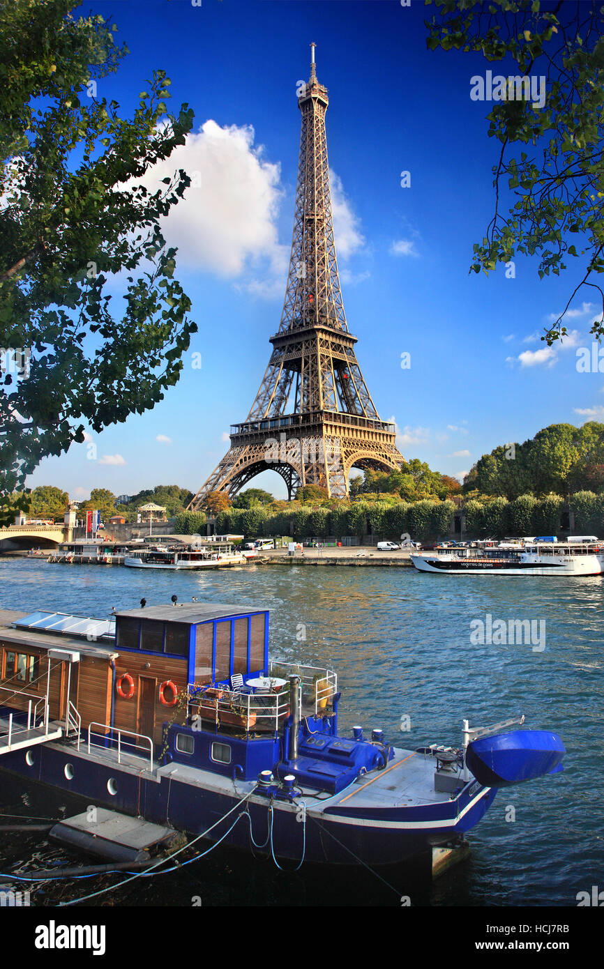 Old riverboat used as residence on Seine river, Paris, France. In the background the Eiffel Tower. - Stock Image