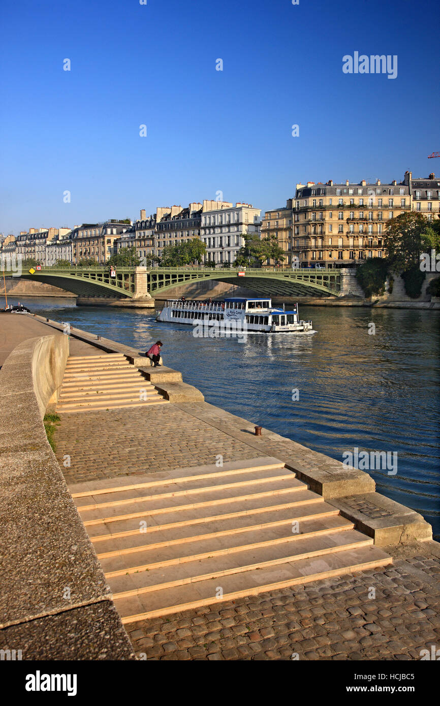 Riverboat passing under Pont de Sully, the bridge that connects Saint-Germaine and Ile Saint-Louis, over Seine river, - Stock Image