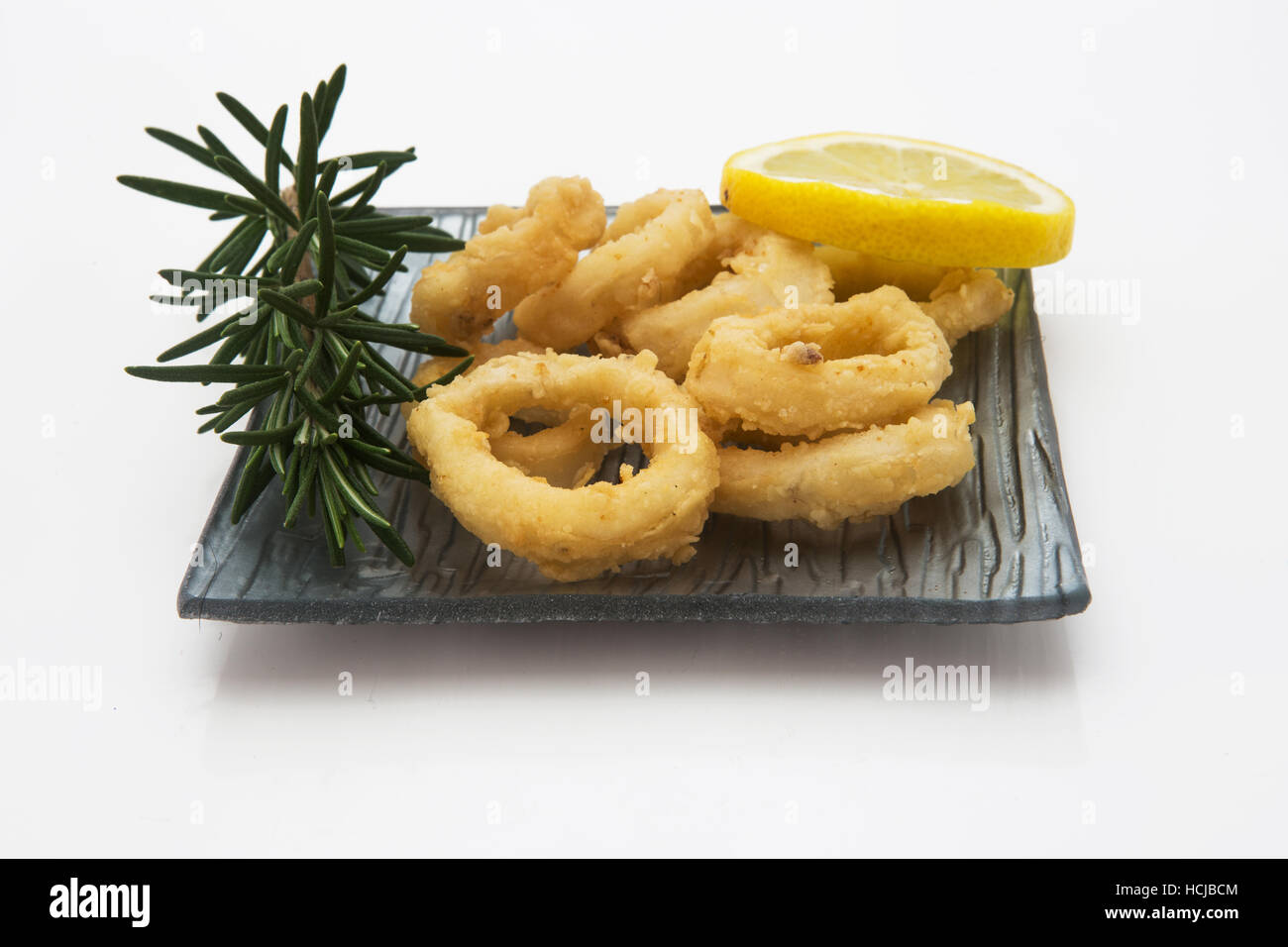 Calamari ring OR Fried squid ring with lemon and sauce - Italian food style isolated on white - Stock Image