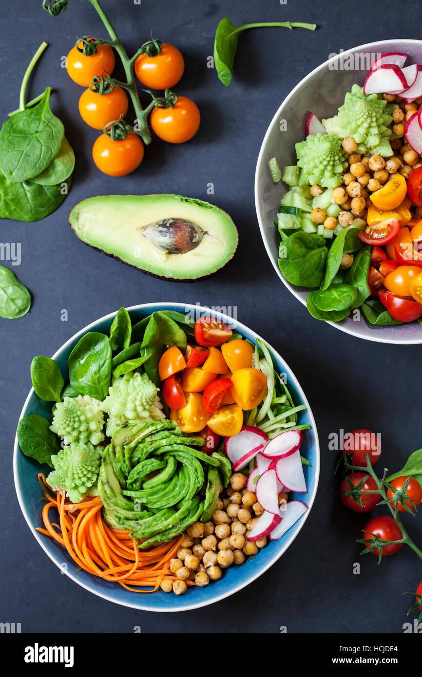 Buddha vegetable bowl with avocado, romanesco cauliflower, carrots, chickpeas, tomatoes and radishes - Stock Image