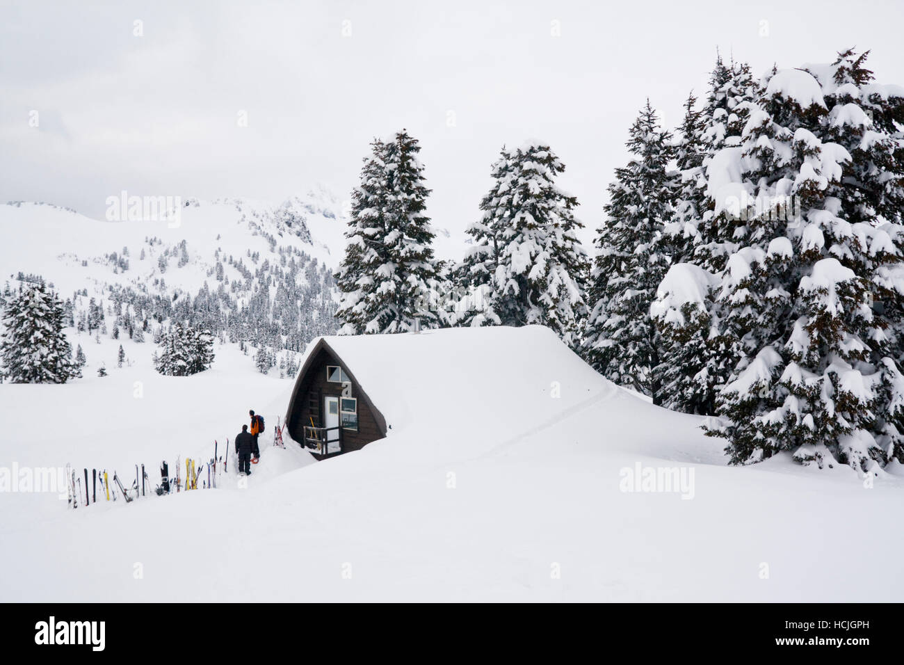 Skiers stand outside the Elfin Lakes Hut, a large shelter in Garibaldi Provincial Park, British Columbia, Canada. Stock Photo