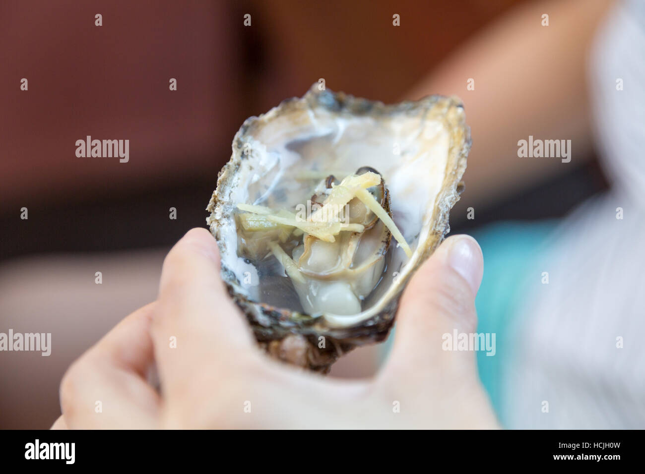 Hand grabs an partially cooked open shell oyster with ginger, Santa Catarina, Brazil - Stock Image