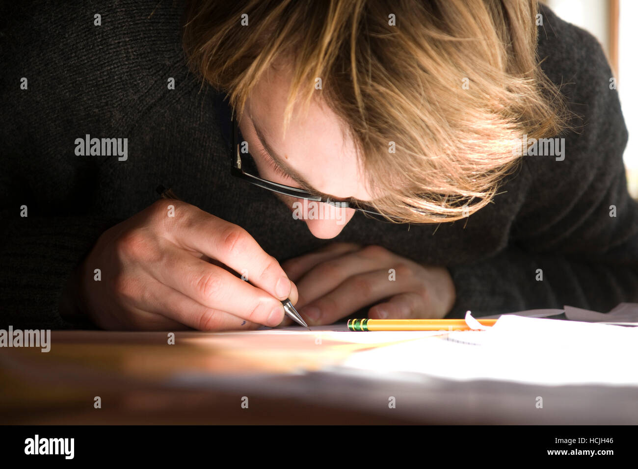 A young man hunched over a desk, intently drawing with a pen. - Stock Image