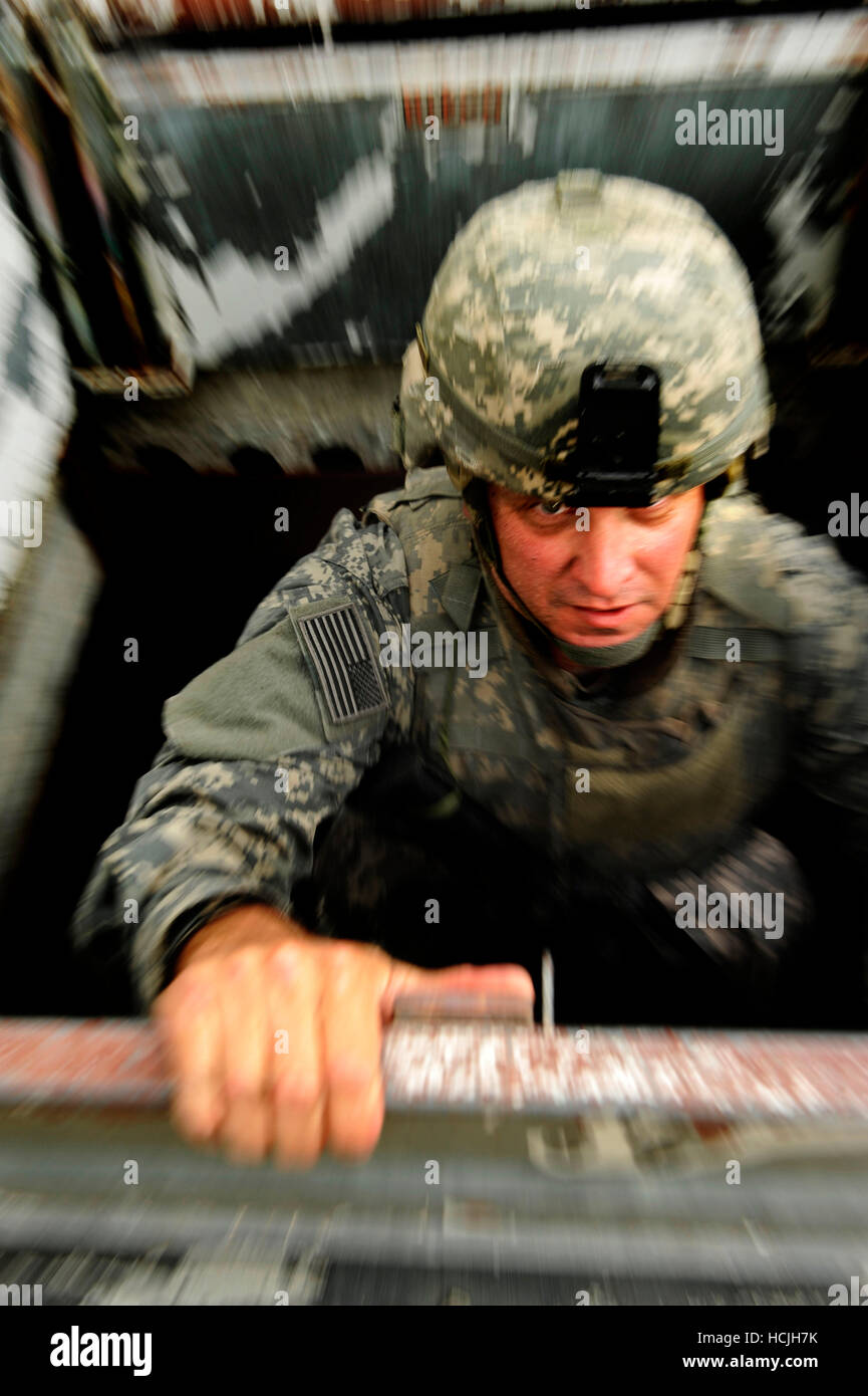 A soldier demonstrates body armor can be light and maneuverable climbing up the ladder of a building. - Stock Image