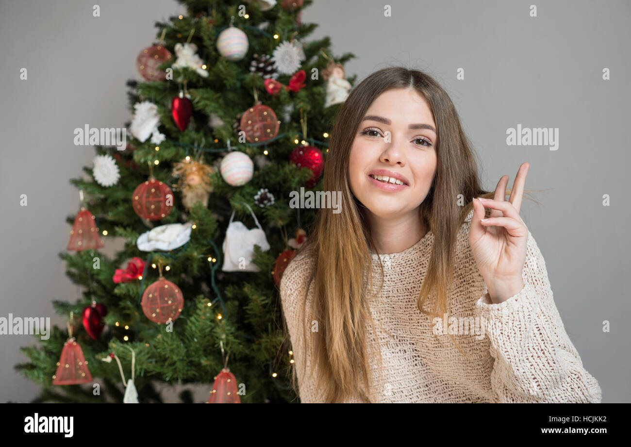 Portrait of a young brown-haired woman near a Christmas tree - Stock Image