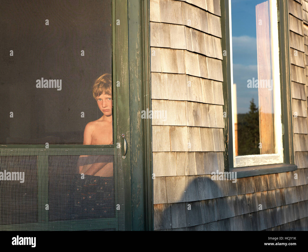 Boy Peaks Out Screen Door At Sunset On Maine Island Stock Photo