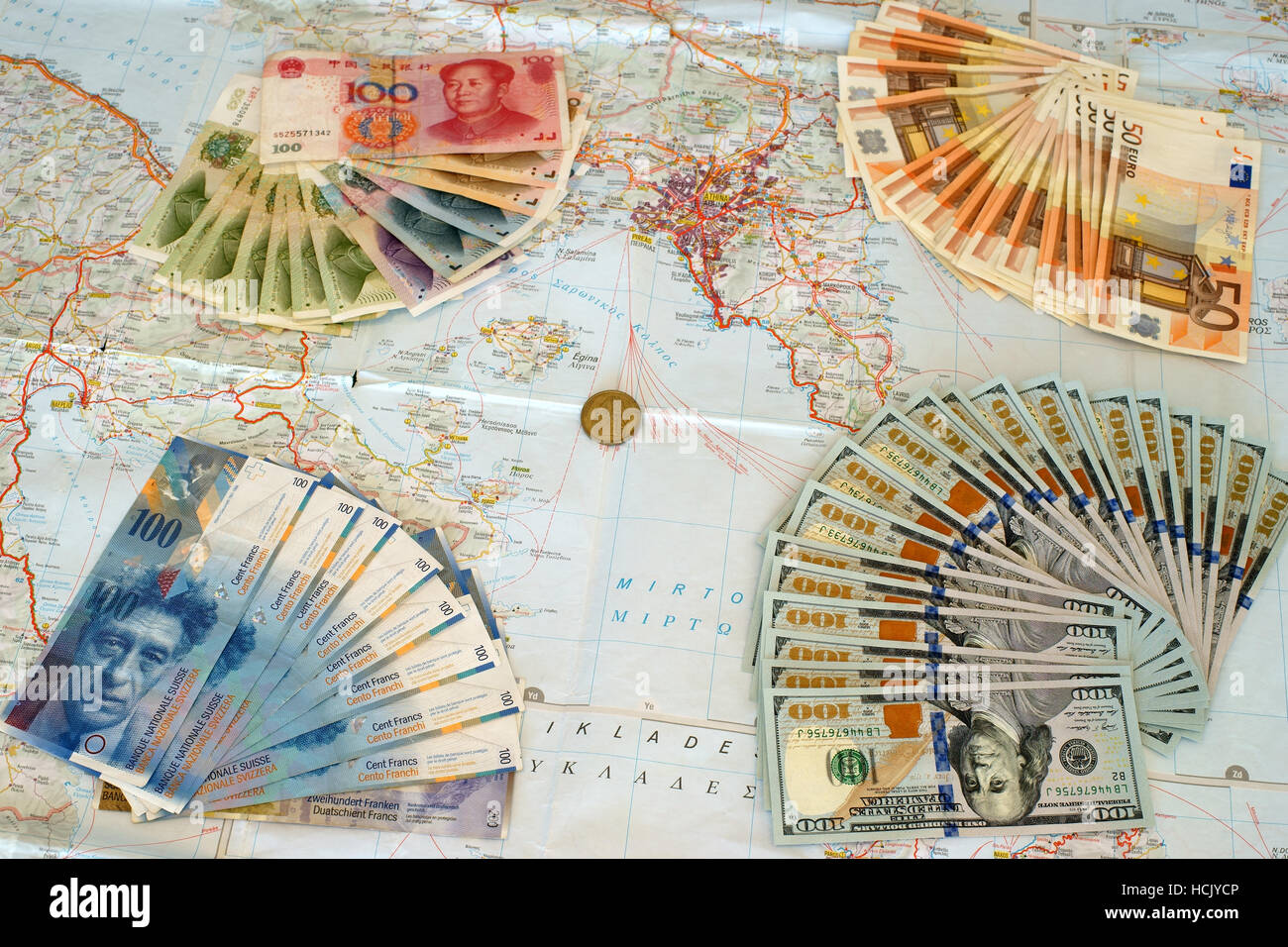Euro, yuan, us dollars and swiss frank banknotes on map of