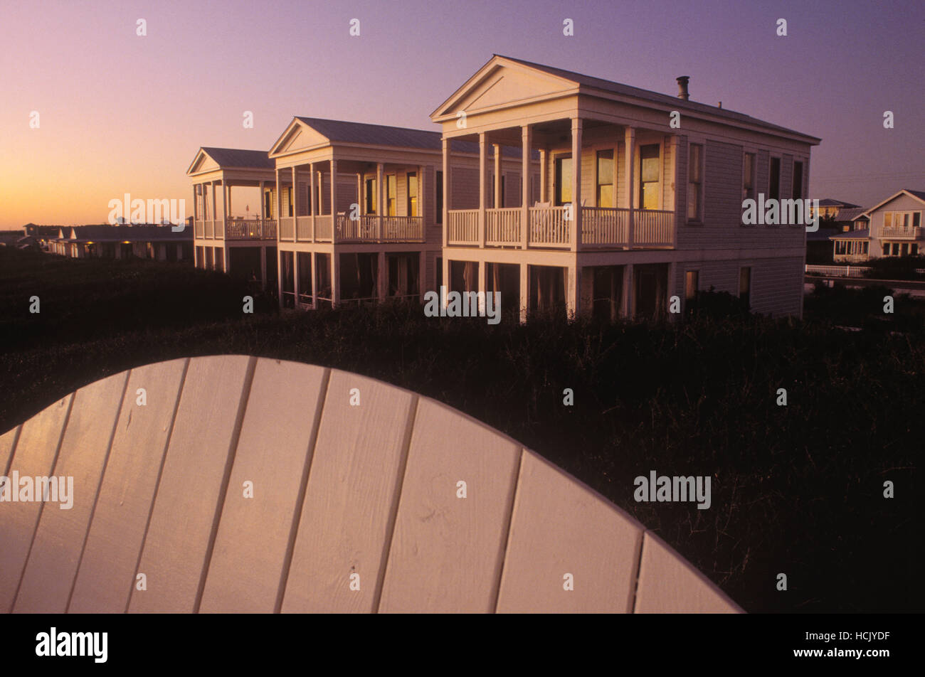 Twilight eliminates three identical wood framed cottages from a bench at the Seaside community in Florida. - Stock Image