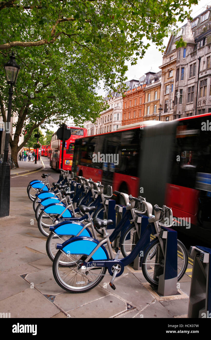 Doubledecker buses drive past a stand of bicycles for hire in central London. Barclays Cycle Hire is a public bicycle - Stock Image