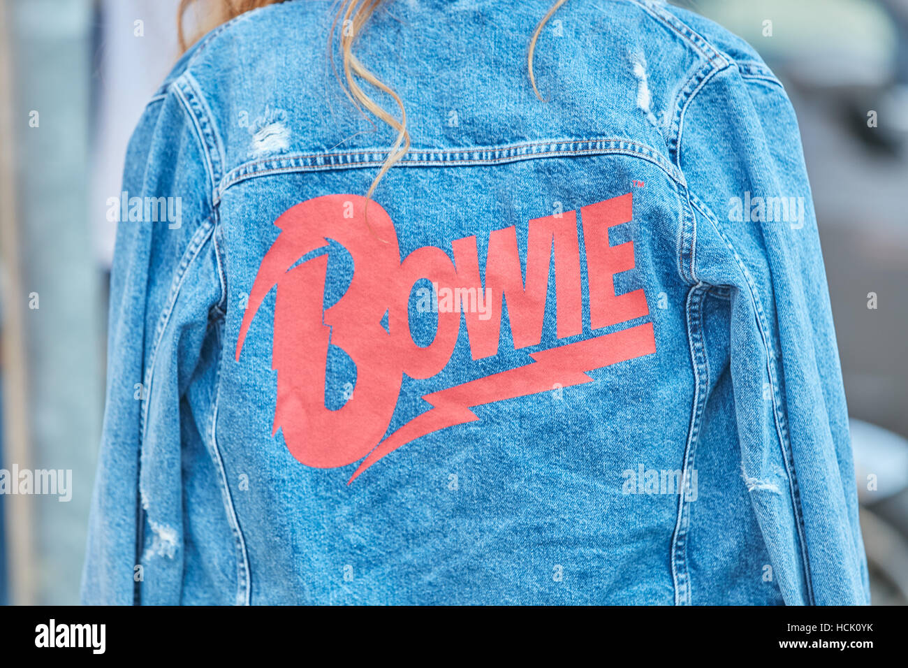 Woman with blue jeans jacket with red Bowie writing before Jil Sander fashion show, Milan Fashion Week street style - Stock Image