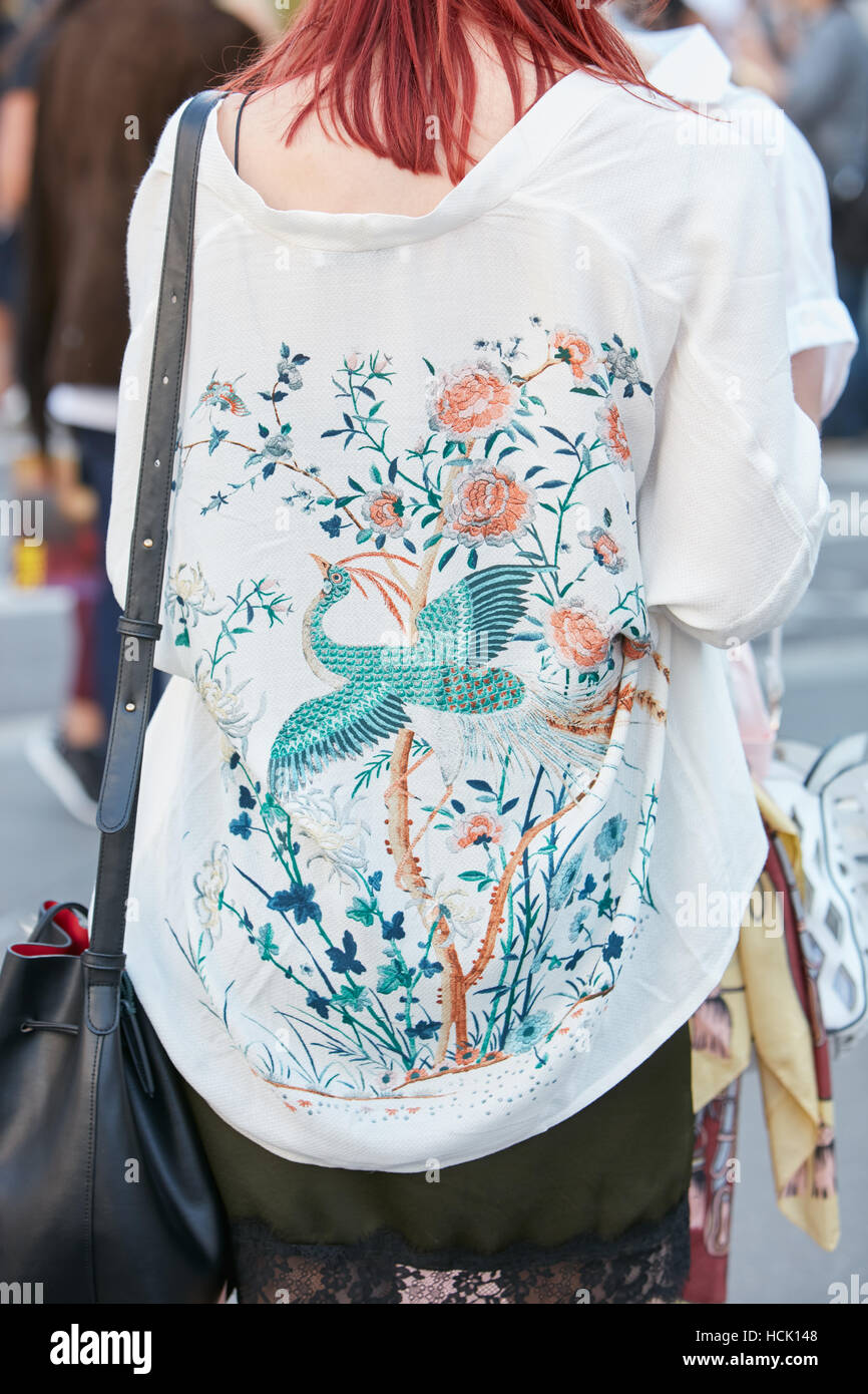 Woman with white shirt with floral design and crane bird before Jil Sander fashion show, Milan Fashion Week street - Stock Image
