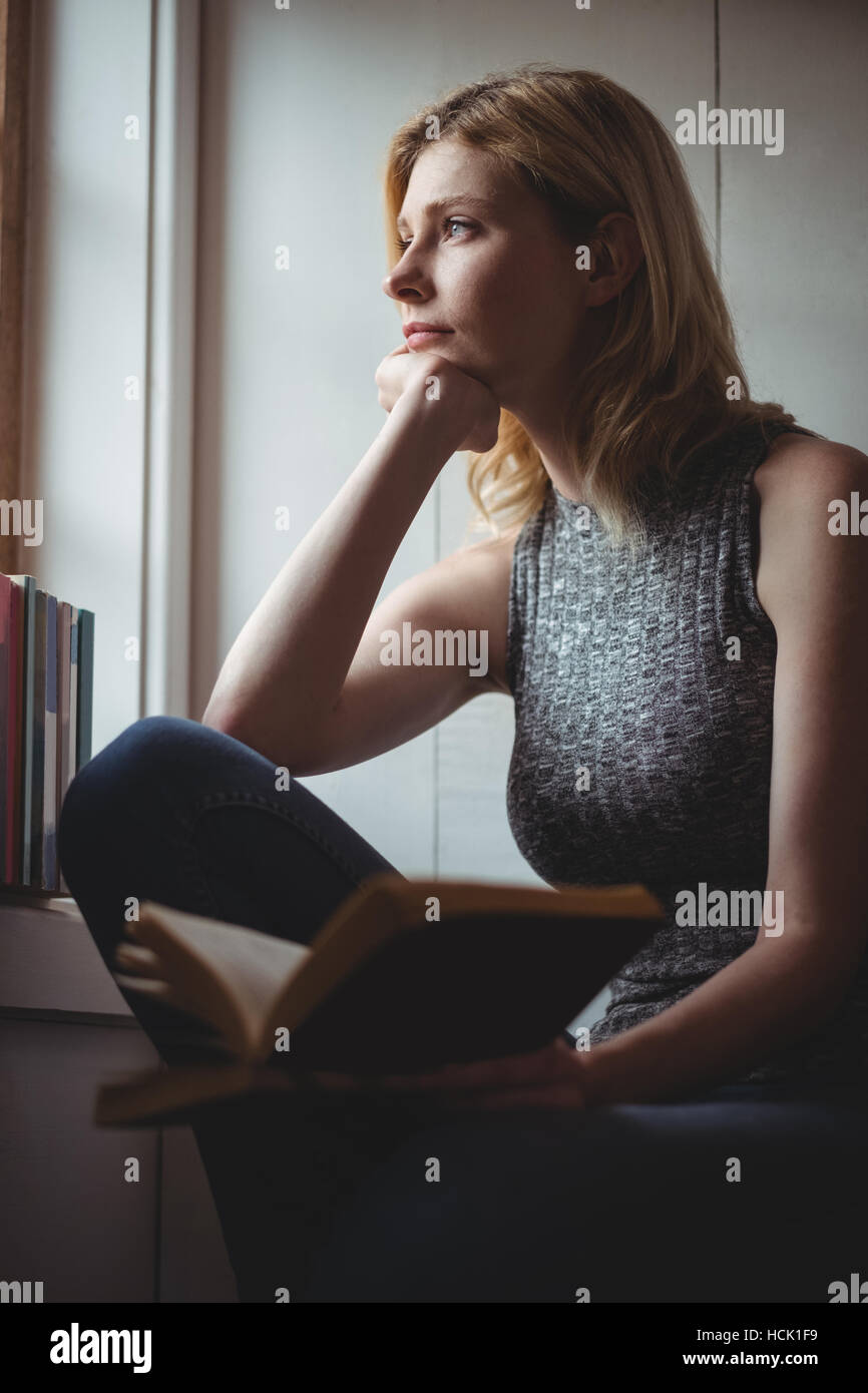 Thoughtful woman looking through window - Stock Image