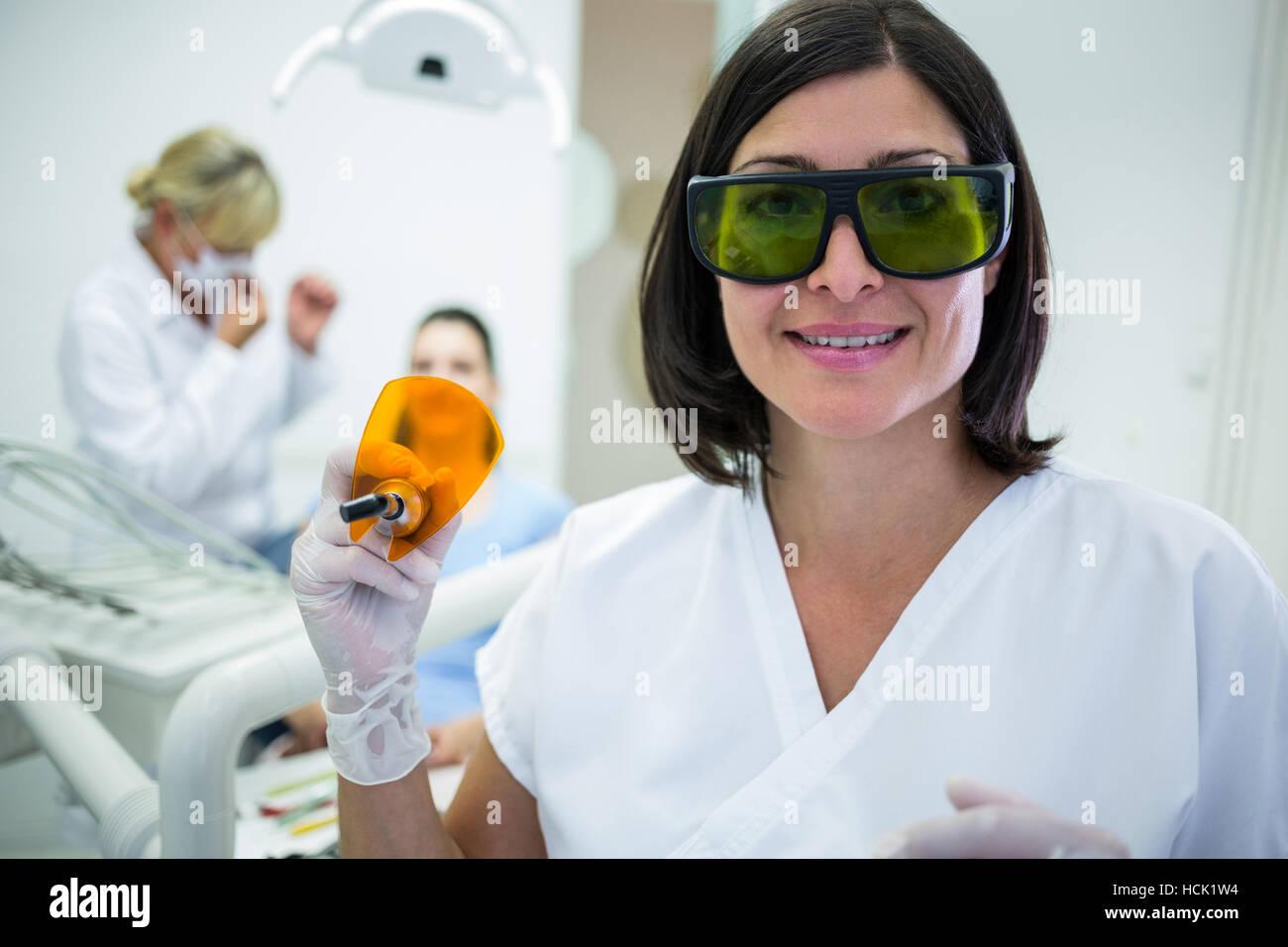 Dentist holding a dental curing ultraviolet light - Stock Image