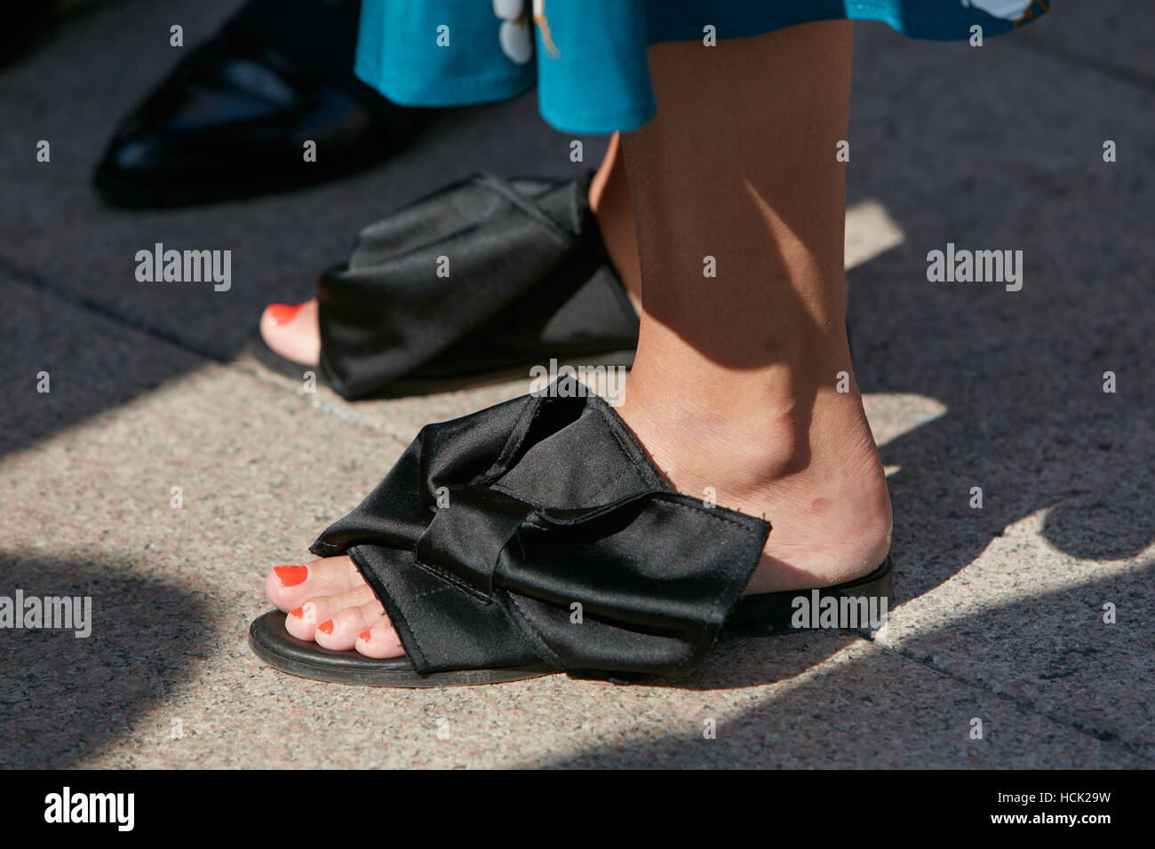 Woman with black ribbon sleepers before Stella Jean fashion show, Milan Fashion Week street style on September 25, - Stock Image