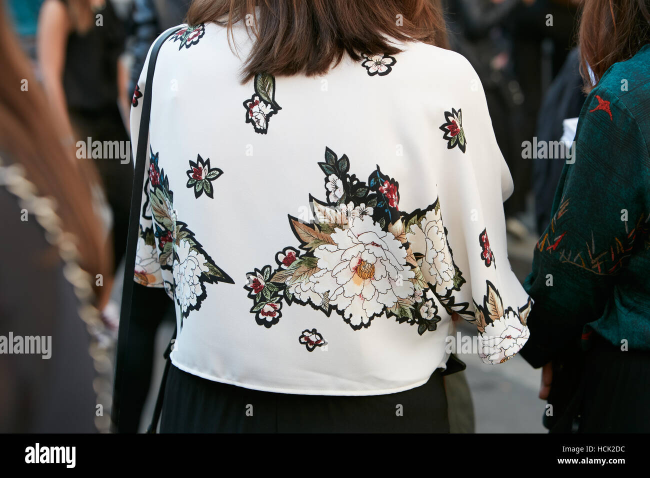 Woman with white shirt with floral design before Salvatore Ferragamo fashion show, Milan Fashion Week street style - Stock Image