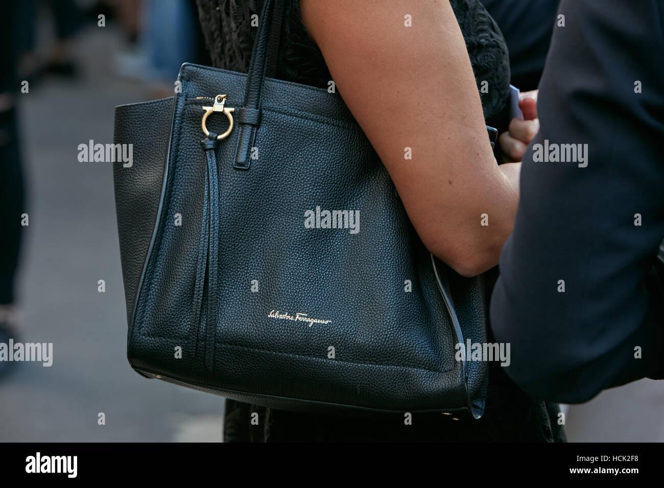 Woman with black leather Salvatore Ferragamo bag before Salvatore Ferragamo fashion show, Milan Fashion Week street - Stock Image