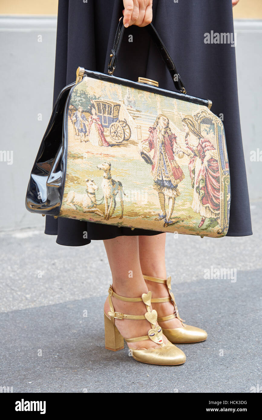Woman with bag with historical print scene and golden high heel shoes before Wunderkind fashion show, Milan Fashion - Stock Image