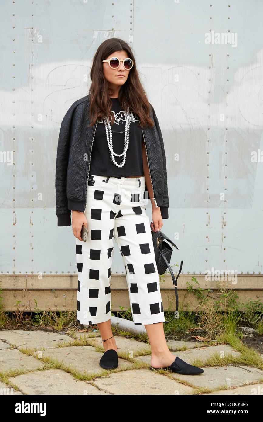 Woman with checkered trousers in black and white before Gucci fashion show, Milan Fashion Week street style on September - Stock Image