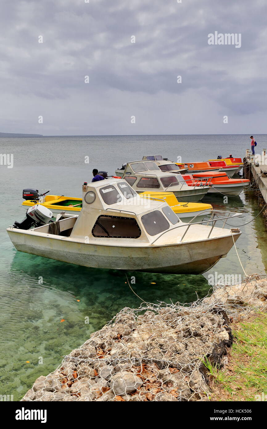 Emua, Vanuatu-October 3, 2014: Local motorboats rest moored to the jetty on the North shore of Efate island while - Stock Image