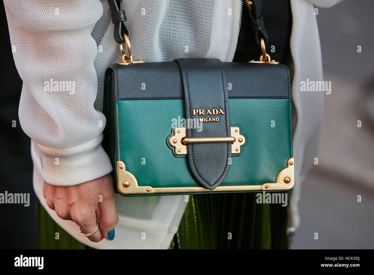 Woman with green and black Prada bag before Prada fashion show, Milan Fashion Week street style on September 22, Stock Photo