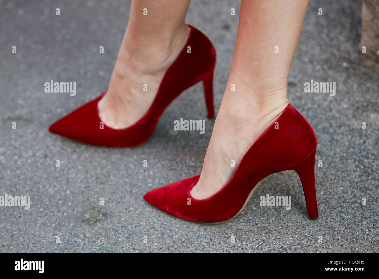 a2c93a910ee Woman with red velvet high heel shoes before Prada fashion show ...