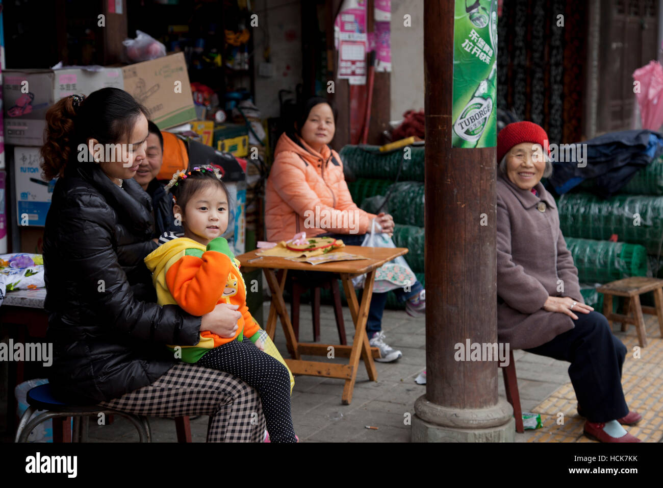 Members of the extended family sitting outside their convenience or general shop in a small old town in west China. - Stock Image