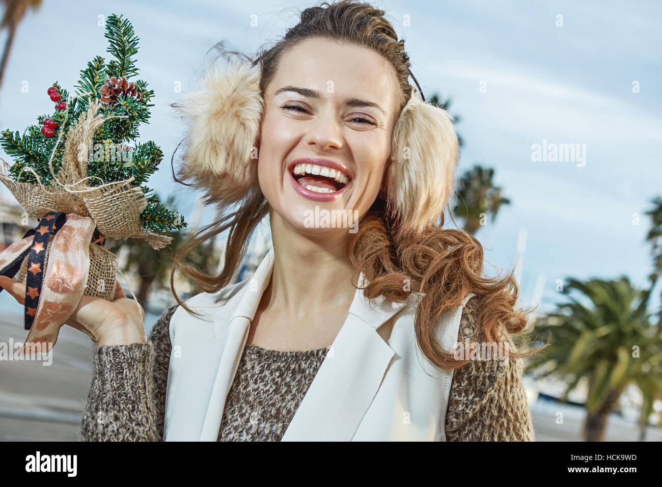in Barcelona for a perfect winter. happy young woman in earmuffs in Barcelona, Spain showing little Christmas tree - Stock Image