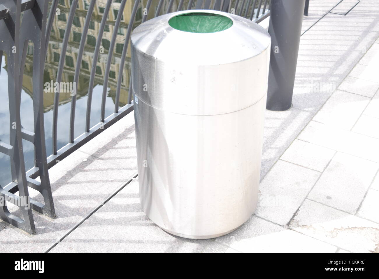 Modern metallic trash bin on the road side - Stock Image