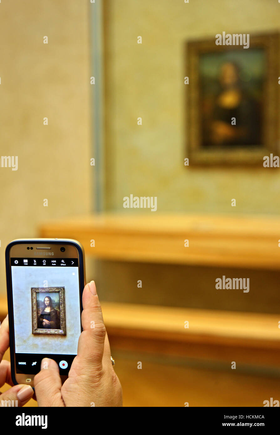 Visitor of the Louvre museum photographing Mona Lisa ('Gioconda') with a smart phone. Paris, France. - Stock Image