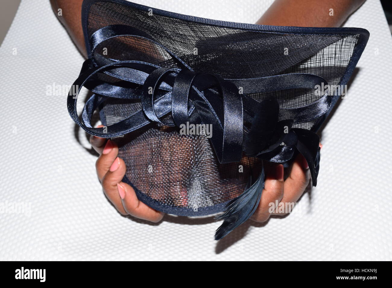 African female hands holding a small, fancy, navy blue hat with a beautiful bow - Stock Image