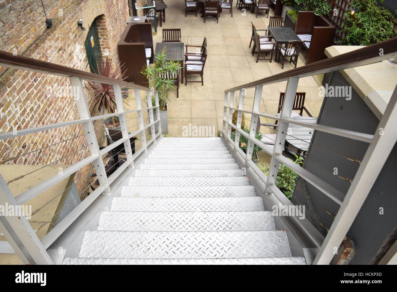 High perspective of stairs going down to meet outdoor restaurant area Stock Photo