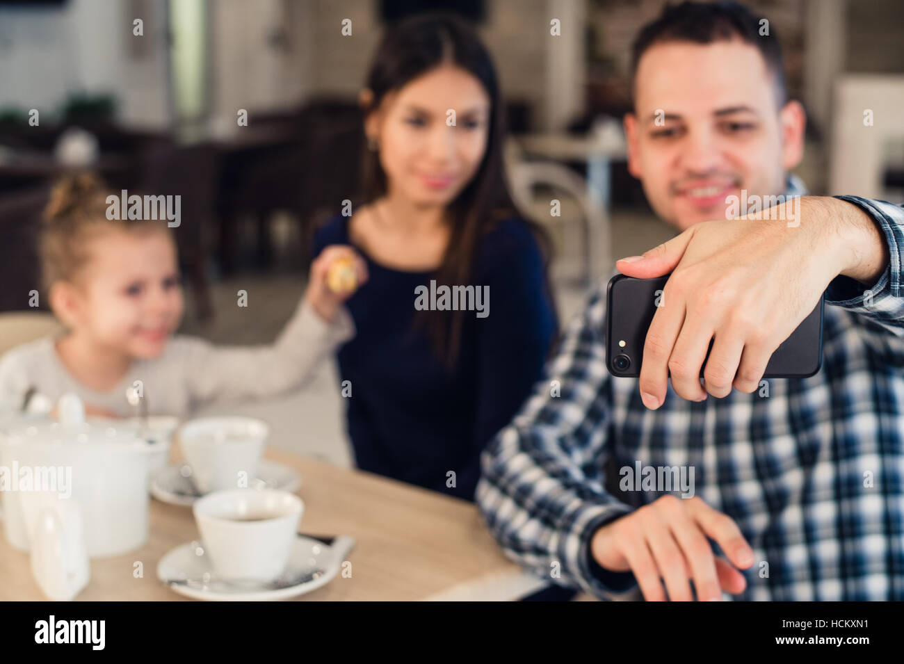 family, parenthood, technology people concept - happy mother, father and little girl having dinner taking selfie - Stock Image