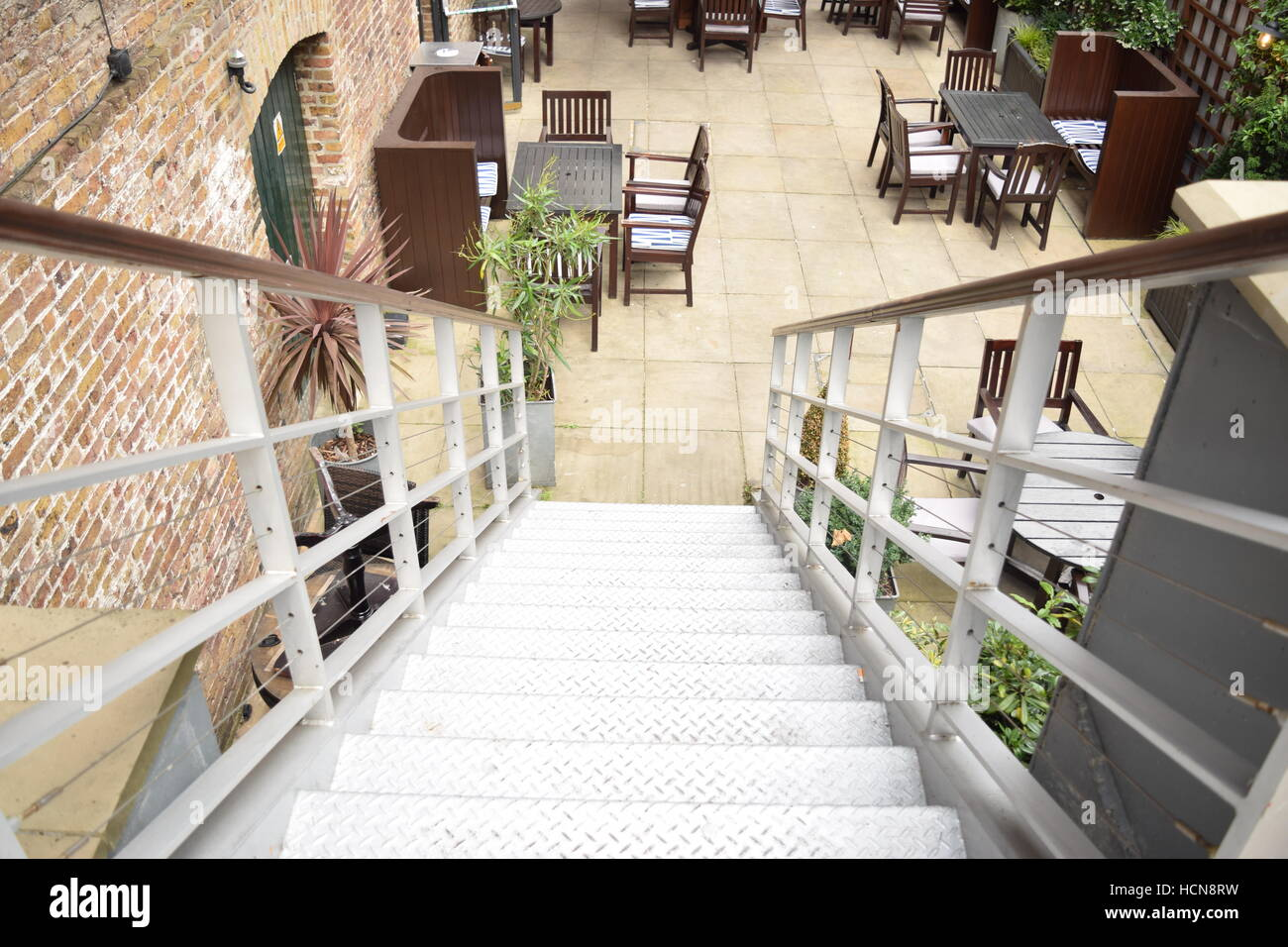 Long flight of stair leading to a outdoors restaurant seating area Stock Photo