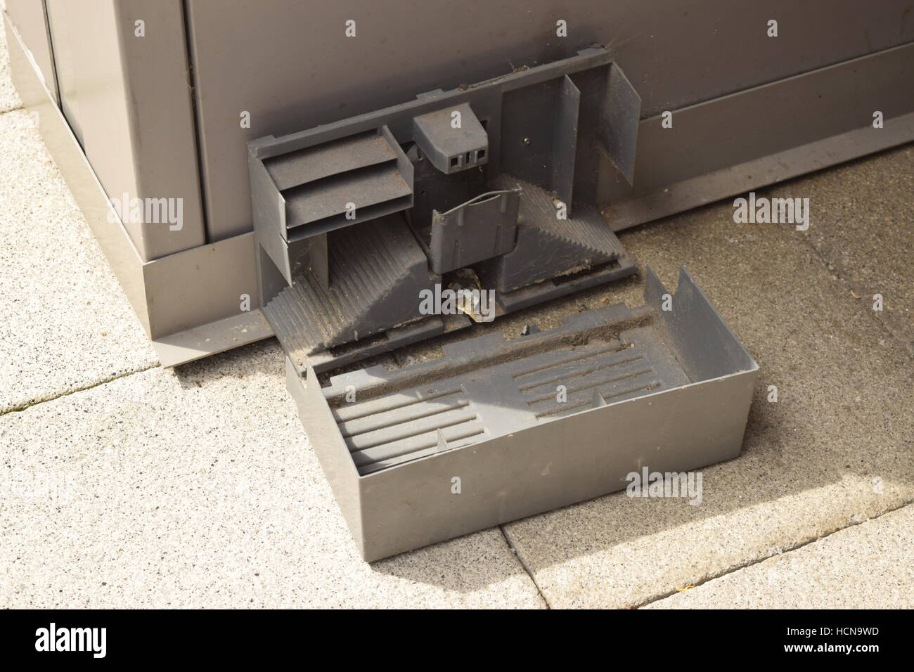 Small broken metal built rat trap on a city district corner - Stock Image