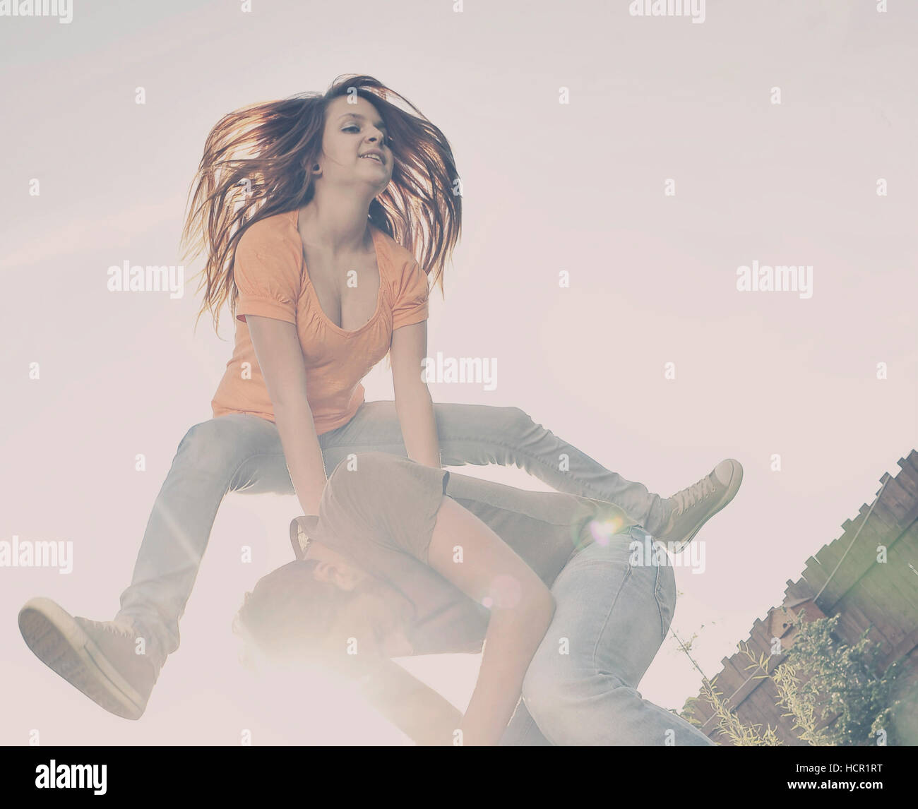 Happy woman excited jumping over a man - Stock Image
