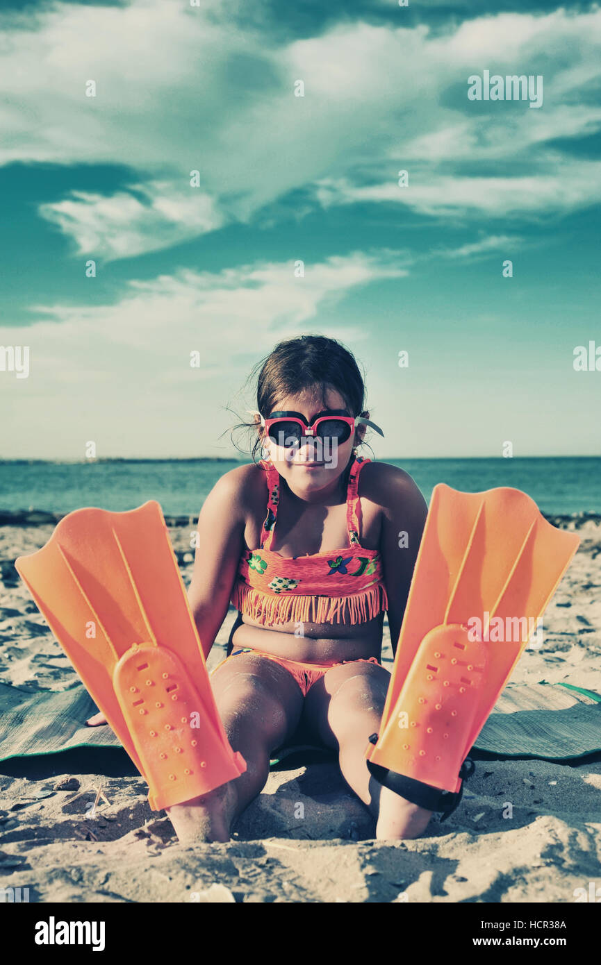 Young girl with flippers standing on beach - Stock Image