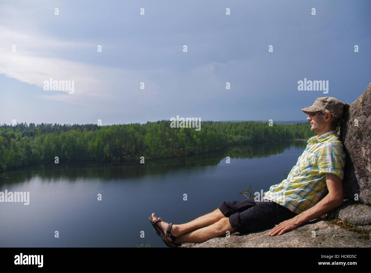 a happy young man sitting on a rocky slope above a lake - Stock Image