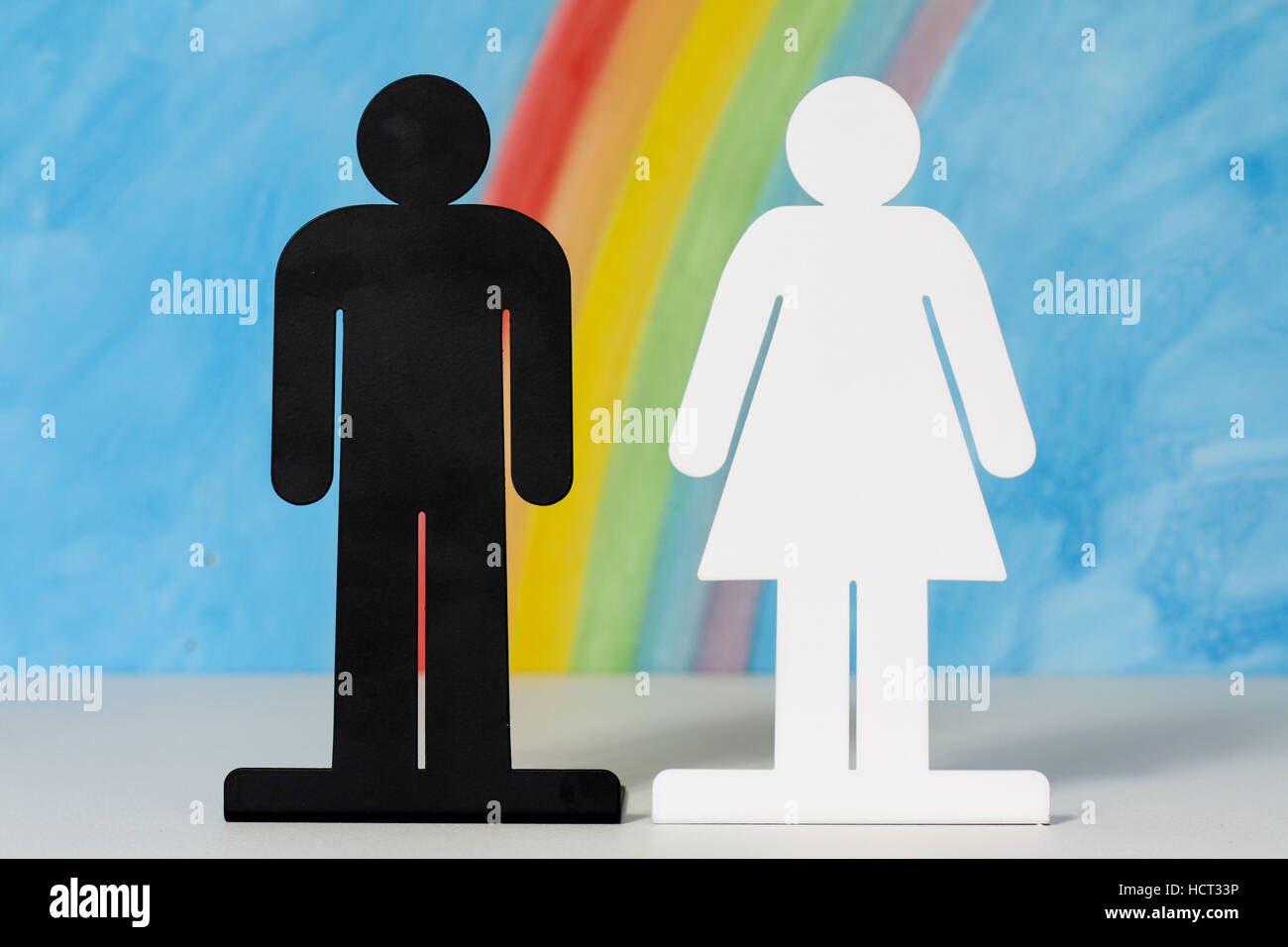 Man and women icons with a rainbow and blue sky to illustrate the concept of marriage, relationships and gender Stock Photo