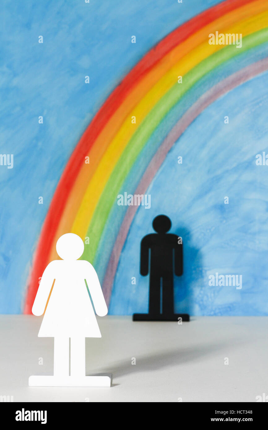 Man and women icons with a rainbow and blue sky to illustrate the concept of gender equality; woman in foreground. - Stock Image