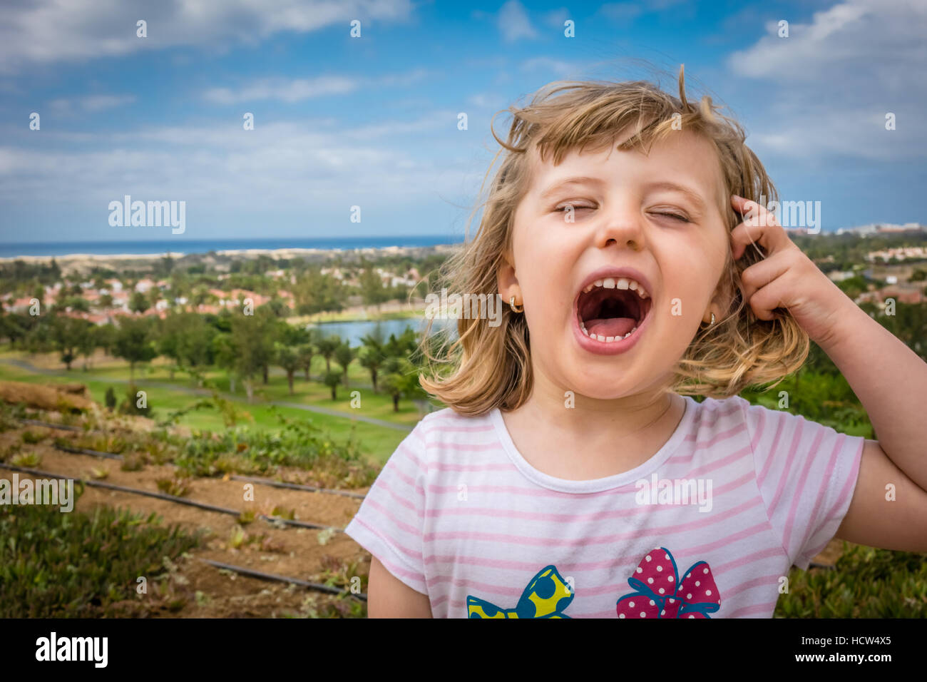 Little girl standing on a viewpoint over Maspalomas in gran Canaria and shouting loudly - Stock Image