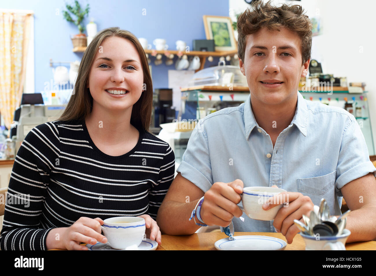 Group Of Portrait Of Teenage Couple Meeting In Cafe - Stock Image