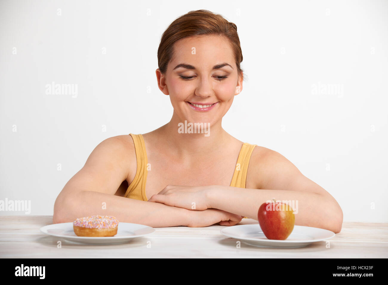 Young Woman Choosing Between Doughnut And Cake For Snack - Stock Photo