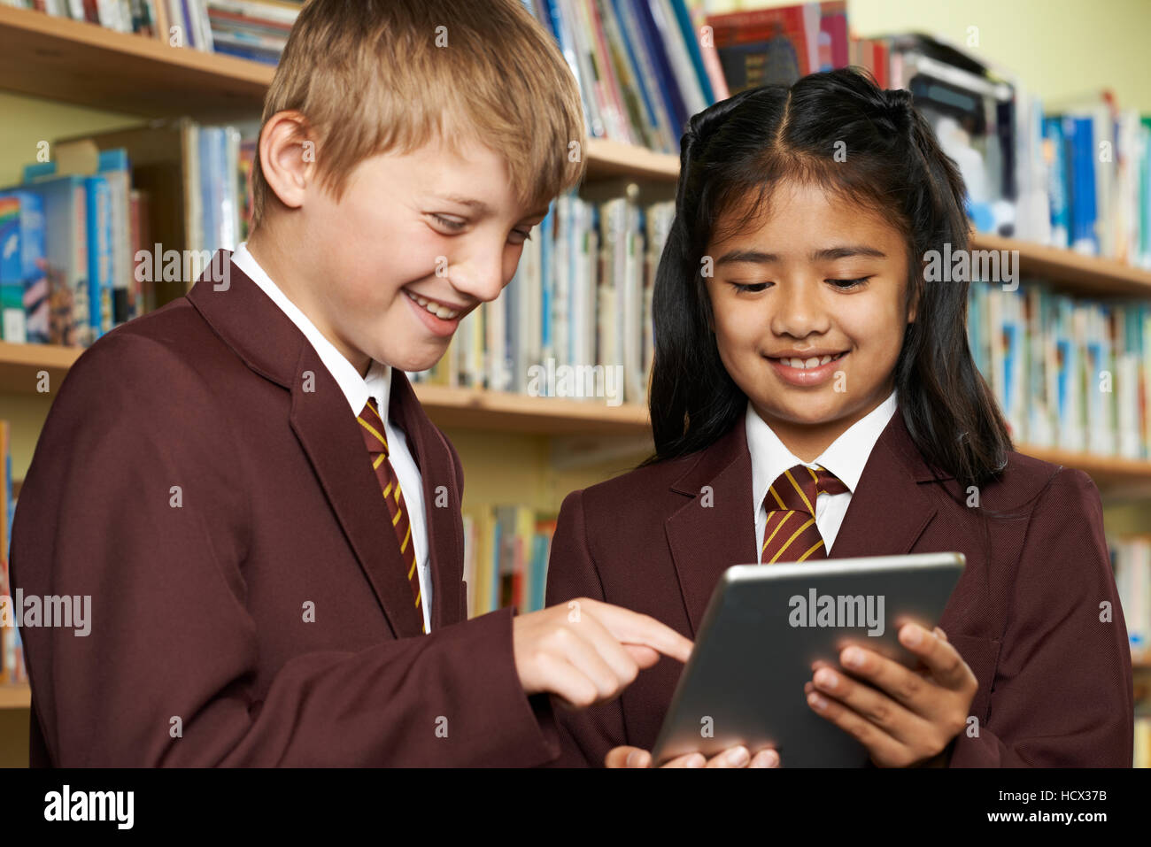 Pupils Wearing School Uniform Using Digital Tablet In Library - Stock Image