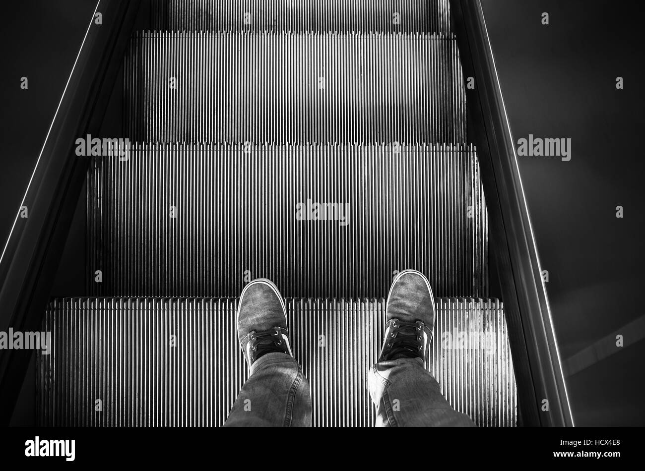 Male feet in canvas shoes stand on escalator stairs, black and white - Stock Image