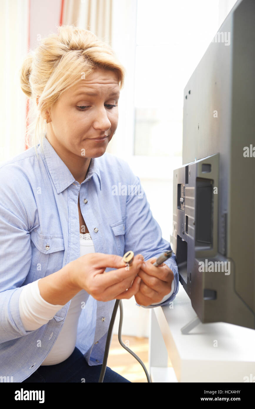Confused Woman Unsure As to How To Put Leads Into New Television - Stock Image